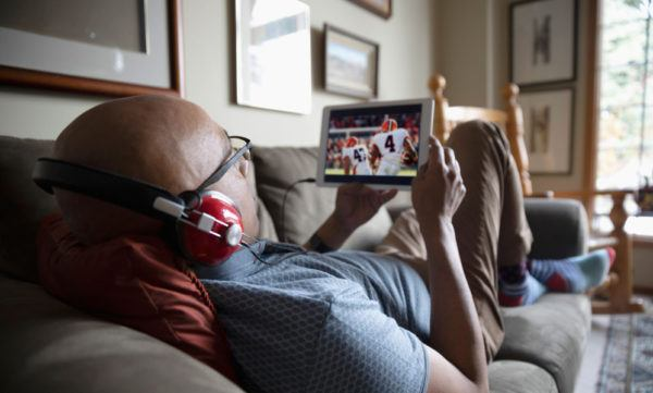 guy watching football on his phone on the couch