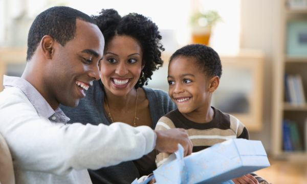 dad opening a present with his wife and son