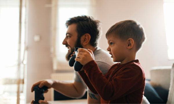 dad and son playing a video game together