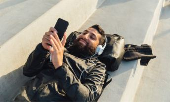 guy laying down listening to music on his phone