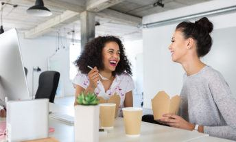 two women eating lunch at their desks and laughing