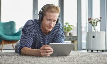 man streaming on his tablet, listening with headphones